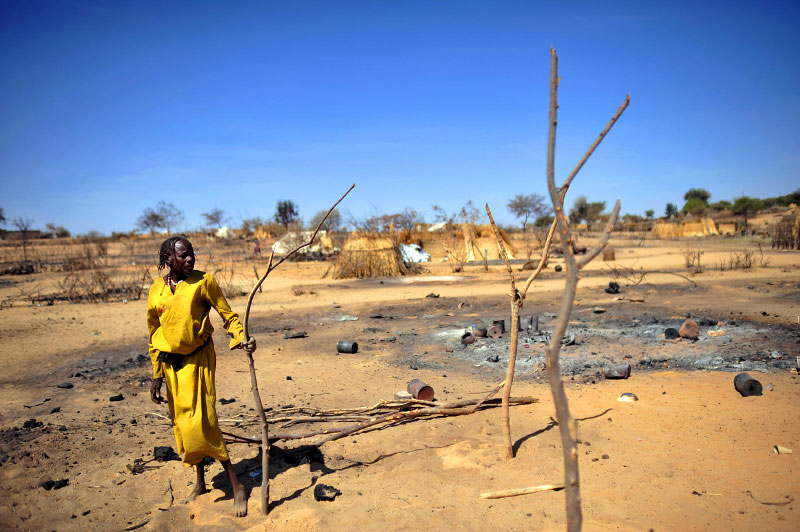 Fadila Ahmed Mohamat stands in the ashes of her home as she and other Sudanese civilians pick through the remains of their burned-out huts, and start to rebuild in the village of Abu Surouj, as troops with the United National African MIssion in Darfur patrol the area, in Abu Surouj, West Darfur, Sudan, February 28, 2008.   Abu Surouj was bombed on February 8, 2008, along with two other villages north of Geneina by the Sudanese government and simultaneously attacked by armed men on camels, horseback and donkeys, otherwise known as Janjaweed, sending thousands of civilians fleeing the area.  The government spate of bombings was in response to an ambush two months prior by rebels from the Justice and Equality Movement, and subsequent intelligence that JEM members were living in these villages and using them as a base. After a period of relative quiet, there has been a great deal of renewed fighting between the Sudanese government with militias loyal to the government and rebel factions, namely JEM. Dozens of civilians in Selean, Sirba, and Abu Surouj were killed in the attacks around February 8th,many others were injured, and a large percentage of each of the three villages was burned to the ground.