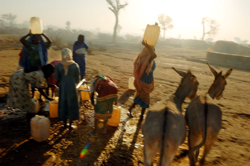 Internally displaced women line up at a water pump for water at dawn at Hamadiya camp in Zallingi, in West darfur, February 2007.  Since the beginning of the war in Darfur, over two million people have been displaced from their villages throughout the region, and hundreds of thousands have been killed.