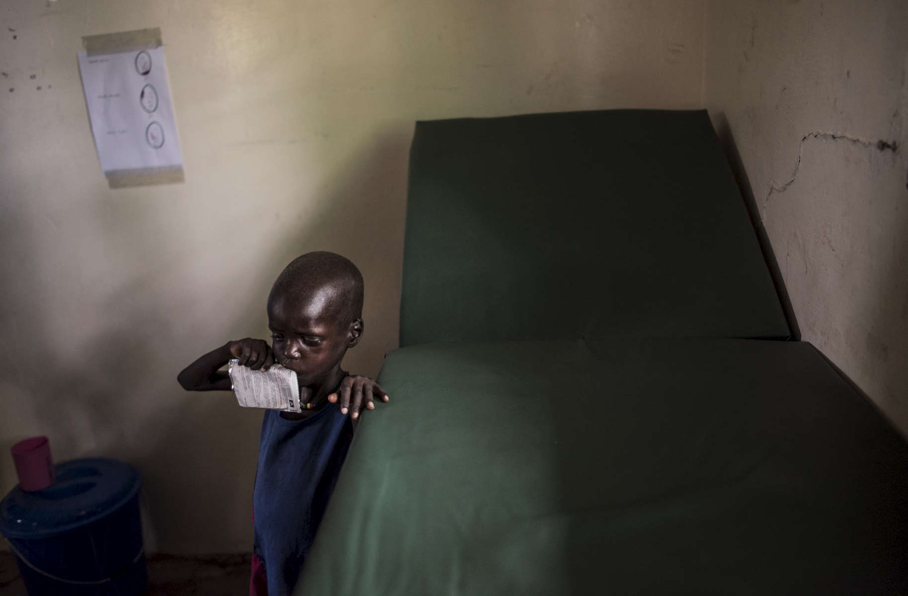 A severely malnourished boy eats a nutrient and calorie-rich packet of food while being treated by medical staff from Doctors without Borders at the MSF hospital in Leer, in Unity State, South Sudan, March 18, 2016.  When fighting raged throughout Leer in 2014 and 2015, most of the population fled, leaving civilians unable to harvest crops,and many struggling to find food. The city of Leer, once a bustling city and headquarters of opposition leader Riek Marchar, is now a ghost town reduced to rubble and the carcases of buildings. (Credit: Lynsey Addario for Time Magazine)