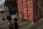 South Sudanese children play in the containers in the Camboni Compound, the presumed location where in October 2015, roughly 50 men were forced into a shipping container by government forces, and held in there for 36 hours until they soffocauted and died in Leer, in Unity State, South Sudan, March 20, 2016.  When fighting raged throughout Leer in 2014 and 2015, most of the population fled, leaving civilians unable to harvest crops,and many struggling to find food. The city of Leer, once a bustling city and headquarters of opposition leader Riek Marchar, is now a ghost town reduced to rubble and the carcases of buildings. (Credit: Lynsey Addario for Time Magazine)