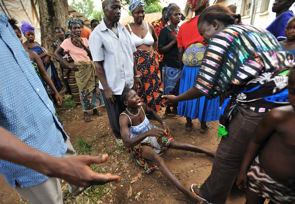 Sessay's mother Marie Yatteh screams with sorrow and falls to the ground when she is told that her younger daughter has died.