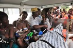 Marie Yatteh, second from left, looks over the body of her daughter, Mamma Sessay, as she breastfeeds her own child. In this photo, they are being transported back to their village in a borrowed ambulance.
