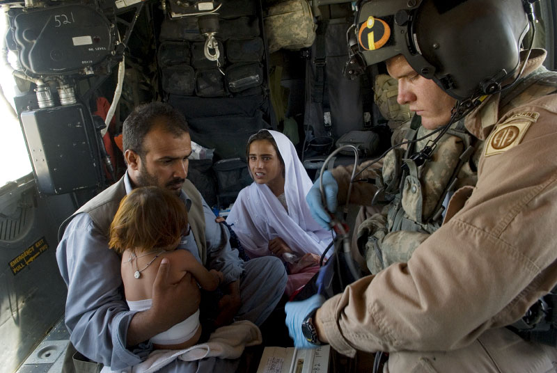 Sgt. Joshue Sands, 23, medic, tends to an Afghan girl, Sophia, 1,  who was burned in an accident in her home as her sister, miriam, 5, holds her, and her father, Abdul Shakur, sits closeby. the medevac team often picks up afghans not injured by coalition forces in order to win 'hearts and minds' of the civilian population, in addition to those they pick up who were injured inadvertently in collateral damage during attacks.  the soldier looking on is a canadian escort for the afghani family to the hospital on kandahar base.