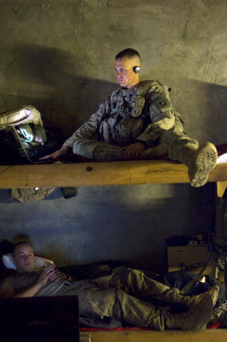 PFC Nikolai Polikolsky, 21, top bunk, a gunner, of riverside, california, listens to music and looks at pictures of his girlfriend.  bottom bunk: PFC rocky tyler, 20, of Atlanta, GA, a driver, watches 'Heros' on dvd during downtime at the KOP forward operating base in Kunar. October 2007. Credit: Lynsey Addario