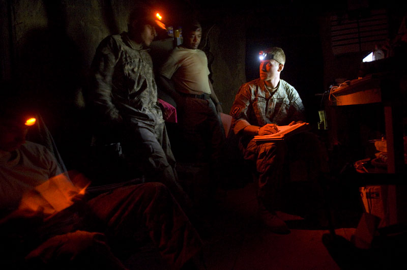Soldiers with the 173rd division ride, first platoon of battle company, look over notes after the evening meeting on the day's happenings. Sgt Chris Shelton, center, looks at Sgt Gallardo, left, as Sgt Sandifer looks on. far left is lt. brad winn at Vegas base, a forward operating base, in the mountains of kunar, afghanistan.  The soldiers use red headlamps to minimize the distance the light travels.