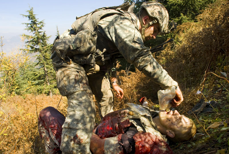 American soldiers with the 173rd battle company, on a battalian-wide mission in the Korengal valley, looking for caves and weapons caches and known Taliban leaders.In photo: Tanner Stichter tends to Specialist Carl Vandeberge in the bushes moments after Vandeberge was shot in the stomach during a Taliban ambush, which killed one soldier, and wounded two others.   Spc. Carl Vandeberge and Sgt. Kevin Rice, the other wounded soldier not shown here, were medevaced out by blackhawk for surgery. October 23, 2007.