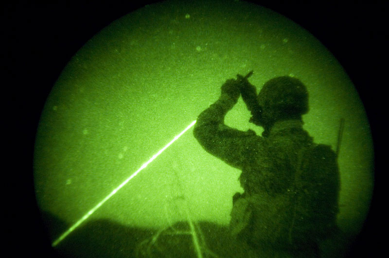American soldiers with the 173rd battle company, on a battalian-wide mission in the korengal valley, Afghanistan.Through night-vision goggles: JTAC Kevin Caroon, 28, 'sparkles' a target for the AC130 pilots above as he helps control close air support fire from above Yakachina village while on a mission with Battle company in the Korengal Valley.  JTACs are Airforce-trained specialists in direct contact with the bomber pilots to call in airstrikes on certain targets while weighing and monitoring collateral damage potential. Captain Dan Kearney, the JTACs, and certain intelligence and communication specialists work as a team from afar but with a bird's eye view to help infantry troops on the ground. October 2007.