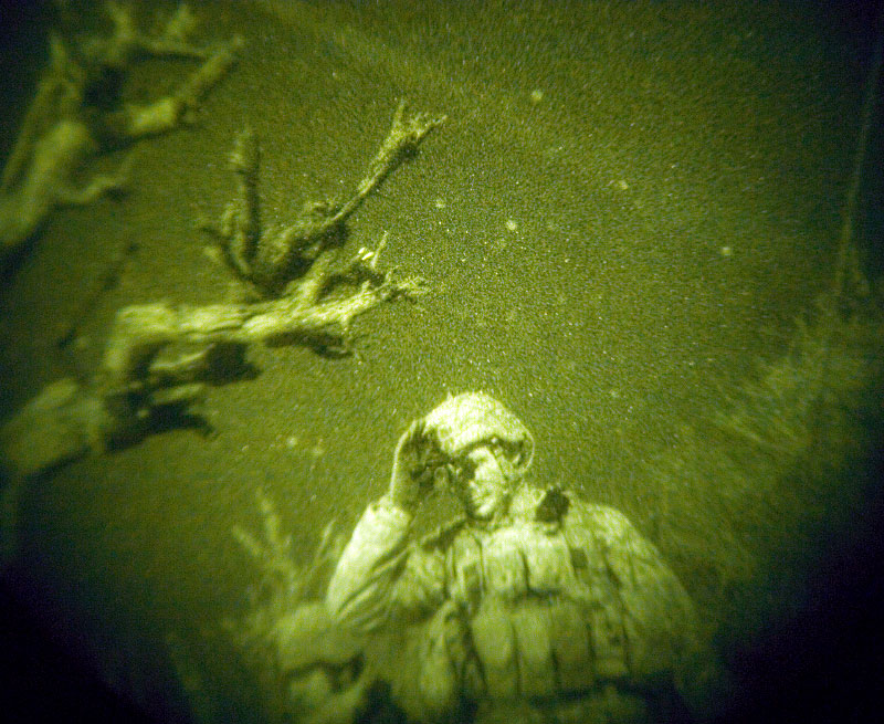American soldiers with the 173rd Division, Battle Company, on a battalian-wide mission in the Korengal valley:Through night-vision goggles: captain Dan Kearney bows his head in frustration as he is denied a bombing request to attack men walking with weapons nearby while he overwatches his troops and controls close air support fire from above while on a mission in the Korengal Valley.  The laser of the AC130 plane is visable tracking the potential target above his head.  On the mission, Captain Keaney works with group of his soldiers and the jtacs, who are Airforce-trained specialists in direct contact with the bomber pilots to call in airstrikes on certain targets while weighing and monitoring collateral damage potential. Dan, the JTACs, and certain intelligence and communication specialists work as a team from afar but with a bird's eye view to help infantry troops on the ground, and the day prior, several civilians had been killed and almost a dozen others injured during their mission in the Korengal valley. October 2007.