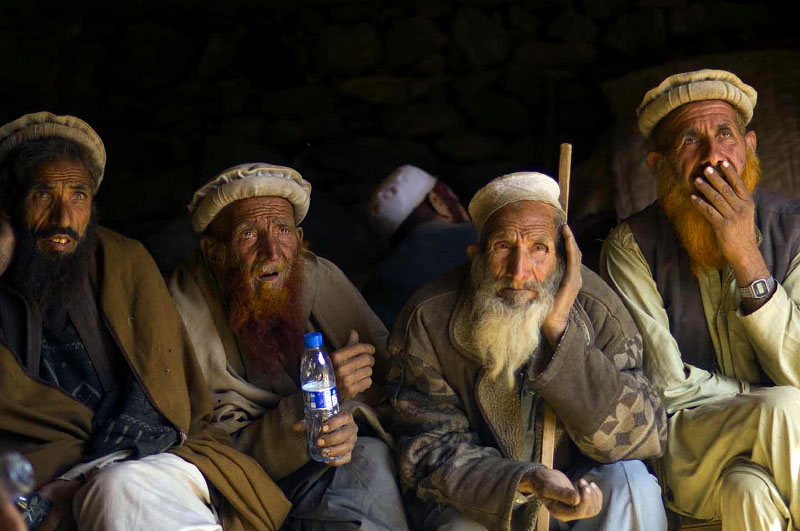 Afghan elders from a 'hostile' village in the Korengal Valley listen to American commanders explain why they had to attack their village with heavy airpower the night before, while on a week-long mission to look for caves, weapons caches, and known anti-coalition members in the Korengal Valley, Afghanistan, October 2007.  The American attacks were prompted after US intelligence picked up armed ACM in the area, and it killed several civilians and injured others.