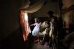 Menja, 5 years old, sits with her mother, Domoina Rahahntanirina, and her brother, in their room in the slums of  Antananivarro, Madagascar, November 9, 2006.  Menja was molested by her uncle one night, and told her mother of the crime, and subseqently identified him in court as the perpetrator. Domoina, who lives with her four children in this one room, did not have enough money to pay the $15. fee for a medical exam for her daughter, facing the same dilemma as many poor Malagassy who do not have enough money to file a case for a victim of sexual assault.  She eventually came up with the money, and the husband of her sister, the perpetrator, is now in jail.