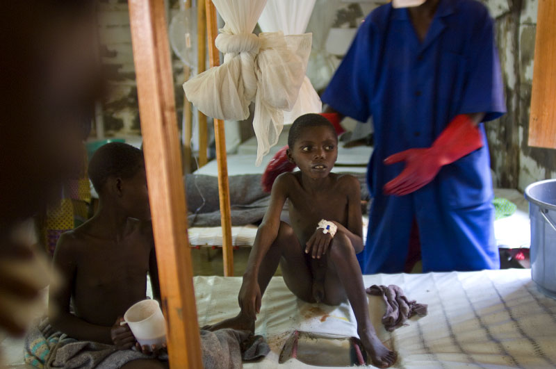 Celestin Mazirane, 9, a displaced boy from Murambe, and Noella, foreground, 12, also displaced, from Rangila, sit sick with Cholera in the MSF-run hospital in Rutshuru, where about 50 Congolese people, most of whom have fled from their villages and are living as internally displaced people in camps or schools, are coming in each day for treatment of Cholera, in the east of the Democratic Republic of Congo, December 10, 2007. Because of ongoing fighting between the government and these militias, thousands of civilians have been displaced from their homes across the region of North Kivu, and are living in dire conditions, without proper sanitation, nutrition, and access to healthcare. In the last 12 months, about 410,000 Congolese civilians have been displaced by new fighting, and coupled with the previous 400,000 from past years, there are now about 800,000 internally displaced people in the DRC.