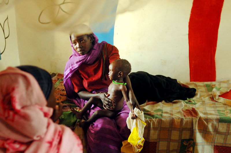 An internally displaced woman holds the bloated stomach of her severely malnourished child before a feeding in the local Zallingi hospital in west Darfur, February 2007.  Since the beginning of the war in Darfur, over two million people have been displaced from their villages throughout the region, and hundreds of thousands have been killed.  Though much progress has been made by NGOs and the United Nations in flighting disease and malnutrition in IDP camps and throughout darfur, many darfurians are still struggling with malnutrition, malaria, respiratory infection, etc.