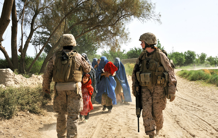 U.S. Marine, Master Sgt. Julia Watson with the Civil Affairs unit attached to the 2/2 Marines, is approached by Afghan women as she patrols through Zanzir village, in the district of Mian Poshteh, Helmand province, Afghanistan.