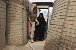 United States marine with the Female Engagement Team, Corporal Diana Amaya, 23, assists an Afghan woman and her grandchildren onto the base for medical treatment at the Cop Sher military base in Mian Poshteh, Southern Helmand, Afghanistan, May 6, 2010.