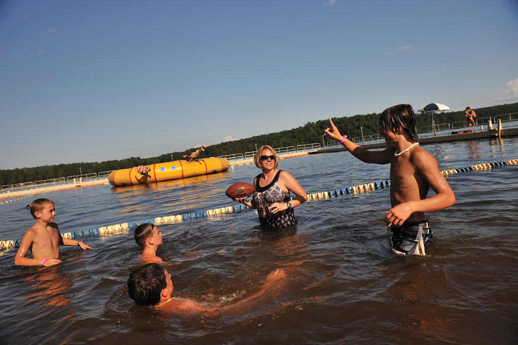 US Soldier MIchelle Sheffield plays football with her son, Brandon, 15. far right,  CJ, 11, and Austin, 10, at the lake in Fort Rucker in Dotham, Alabama, June 25, 2010. Michelle is a blackhawk pilot with the 82nd airborne.