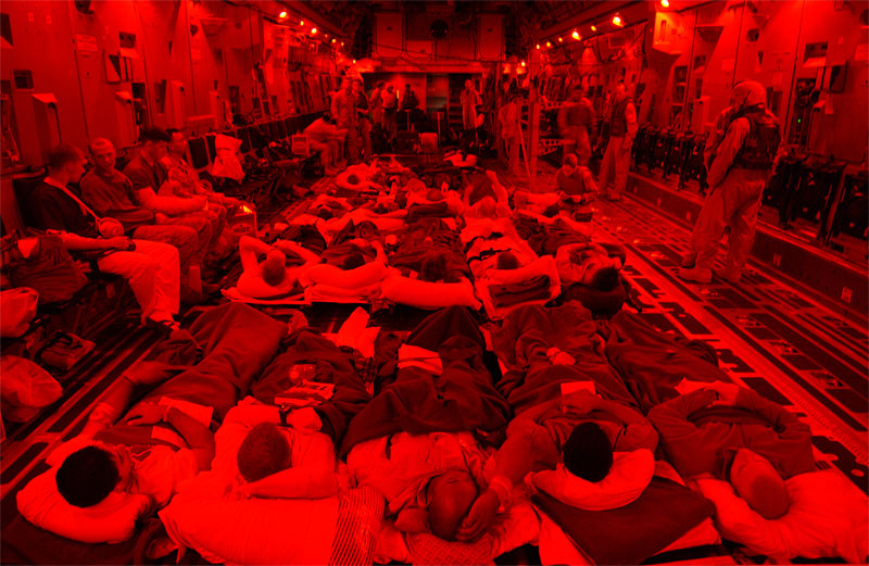 United States Military personnel help load injured soldiers onto a cargo plane en route to Germany from the Balad Air Force base, in Iraq. The interior lights of the plane are red because of an 'alarm red' attack, which indicates that the base is under attack, usually by incoming mortar rounds. Since the attack on Fallujah began in early November, hundreds of soldiers have been injured and evacuated from the country.  November 13, 2006