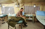 United States PFC Justin Hileman sits with shrapnel wounds to the face in the Balad Hospital at the Balad Air Force base in Iraq. Hundreds of wounded soldiers have come through the military hospital for emergency treatment since the siege of Falujah began in early November.  November 15, 2004