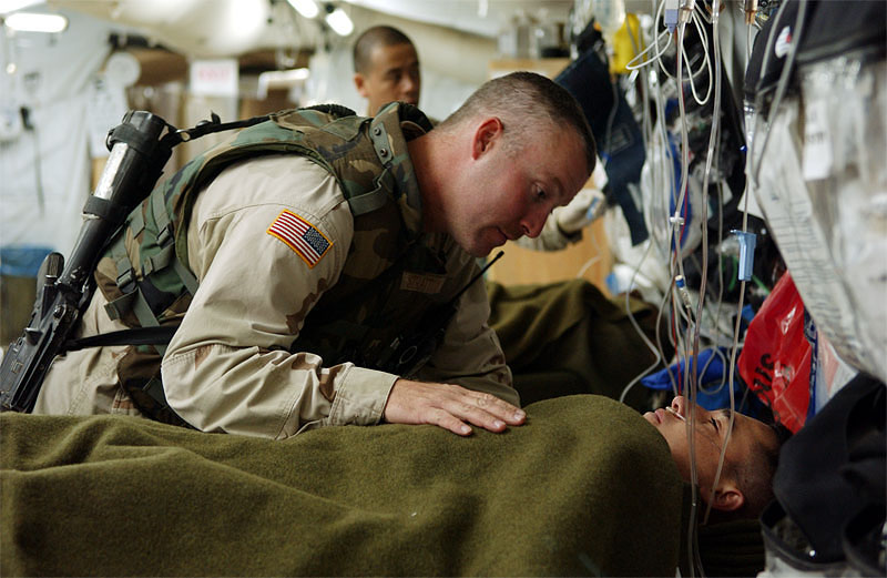United States soldier 1st Sgt. Robert Stratton, 35, visits with an injured fellow soldier after his supply mission was mortared on its way north. Both soldiers are with the National Guard out of Ohio. Hundreds of wounded soldiers have come through the military hospital for emergency treatment since the siege of Falujah began in early November.