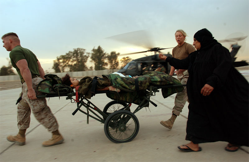 An Iraqi woman runs after her daughter as they arrive on the helipad at the Balad Hospital after their house was hit by mortars, injuring both of her daughters in Iraq. Hundreds of wounded soldiers have come through the military hospital for emergency treatment since the seige of Falujah began in early November.