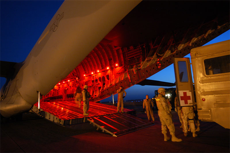 United States Military personnel load injured soldiers onto a cargo plane en route to Germany from the Balad Air Force base, in Iraq. The interior lights of the plane are red because of an 'alarm red' attack, which indicates that the base is under attack, usually by incoming mortar rounds. Since the attack on Fallujah began in early november, hundreds of soldiers have been injured and evacuated from the country.