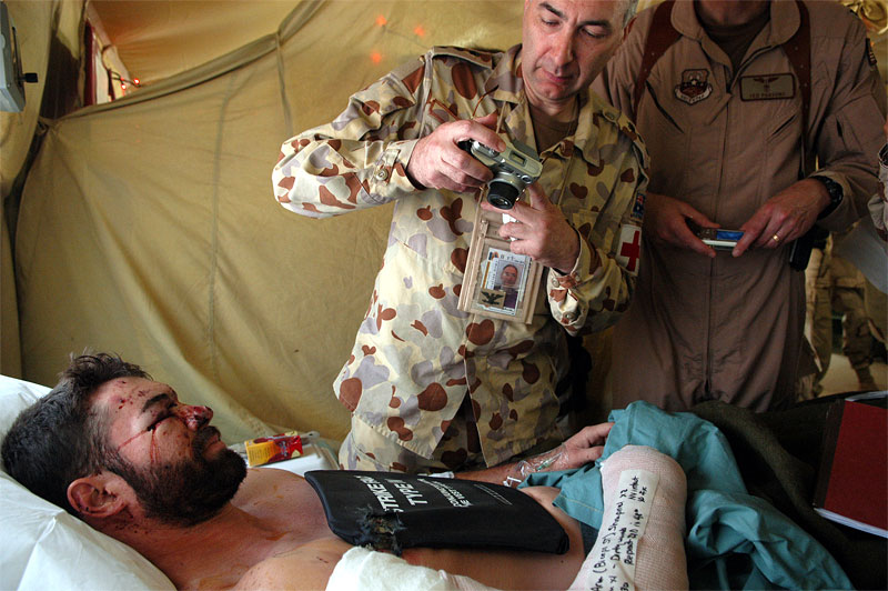 An Australian doctor in the Balad Air Force base in Iraq photographs United States private contractor Jake Guevara. Insurgents ambushed Guevara, along with his team, when they went to pick up people from the embassy, and one of his team was shot and killed instantly. Hundreds of wounded soldiers have come through the military hospital for emergency treatment since the siege of Falujah began in early November.