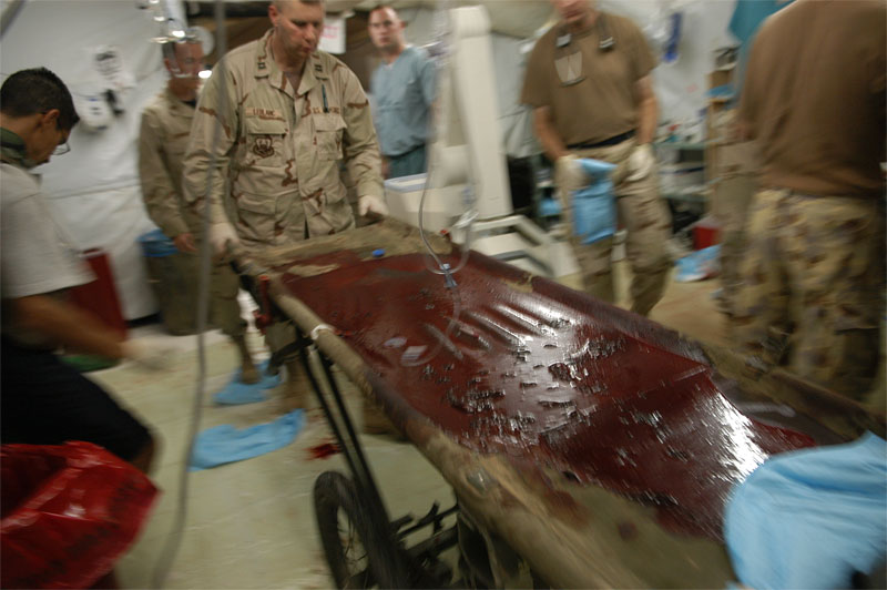 A United States Military soldier pushes a stretcher soaked with blood thru the Emergency room of the Balad Hospital at the Balad Air Force base in Iraq. Hundreds of wounded soldiers have come through the military hospital for emergency treatment since the siege of Falujah began in early November.
