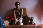 Mable Mutamba, 37, a breast cancer patient, poses for a potrait at her sister's home in between chemotherapy sessions for a tumor that has burst through the skin, in Kampala, Uganda, July 21, 2013.  Mable, like so many other women in Uganda, waited until her cancer was in the advnaced stages, and the tumor had burst through her skin and eaten away a large part of her breast, before seeking medical care at the Cancer Institute.  She found a lump in her breast roughly two years before, and tried traditional medicine consisting of boiled herbs, which proved unsuccessful.  While Uganda was able to get a handle on the AIDs epidemic through ARV drugs and assistance from the international community, the country still struggles with how to treat and diagnose an overwhelming number of Cancer patients across the country.  Thousands are currently being treated by only a handful of trained Oncologists in the entire country of Uganda; basic chemotherapy and Cancer medicines are often in short supply or unavailable, the radiation machine is outdated, in-patient beds are limited, and most Cancer patients can not afford transportation fare to reach diagnosis and treatment in Kampala from villages across the country.