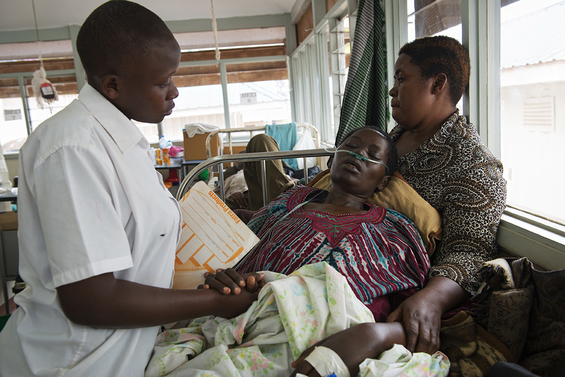 Breast Cancer patient Jolly Komurembe, 38, lies dying as her sister, Peace Magoba, cares for her, and Jolly's daughter, Martha Tumuhekyi, 15, says goodbye for the last time before going back to boarding school in the Solid Tumor Ward of the Cancer Institute attached to the Mulago Hospital, in Kampala, Uganda, July 21, 2013.  Jolly, who has four children with her husband Robert, found a tumor around two years before while living in the western Uganda district of Rukunghiri. Like so many women in Uganda who don't seek medical care for diagnosis and treatment in the early stages of Cancer, Jolly's cancer was advanced when she finally had a mastectomy in January 2013.  These images depict the final week of her life.