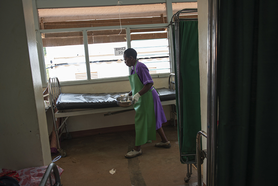 A nurse wipes down the former bed of breast cancer patient Jolly Komurembe, 38, minutes after she passed away in the Solid Tumor Ward of the Cancer Institute attached to the Mulago Hospital, in Kampala, Uganda, July 17, 2013.  Jolly, who has four children with her husband Robert, found a tumor around two years before while living in the western Uganda district of Rukunghiri. Like so many women in Uganda who don't seek medical care for diagnosis and treatment in the early stages of Cancer, Jolly's cancer was advanced when she finally had a mastectomy in January 2013.  These images depict the final week of her life.