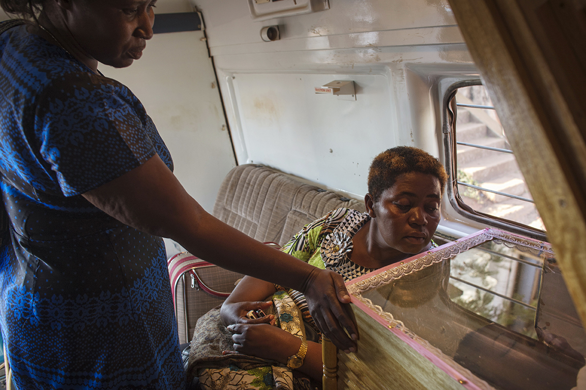 Adrine Ashaba and Peace Magoba look at the dead body of their sister, Jolly Komurembe, 38, hours after she died of advanced breast cancer and before being transported to her village for burial in Western Uganda, in Kampala, Uganda, July 21, 2013.  Jolly, who has four children with her husband Robert, found a tumor around two years before while living in the western Uganda district of Rukunghiri. Like so many women in Uganda who don't seek medical care for diagnosis and treatment in the early stages of Cancer, Jolly's cancer was advanced when she finally had a mastectomy in January 2013.  These images depict the final week of her life.