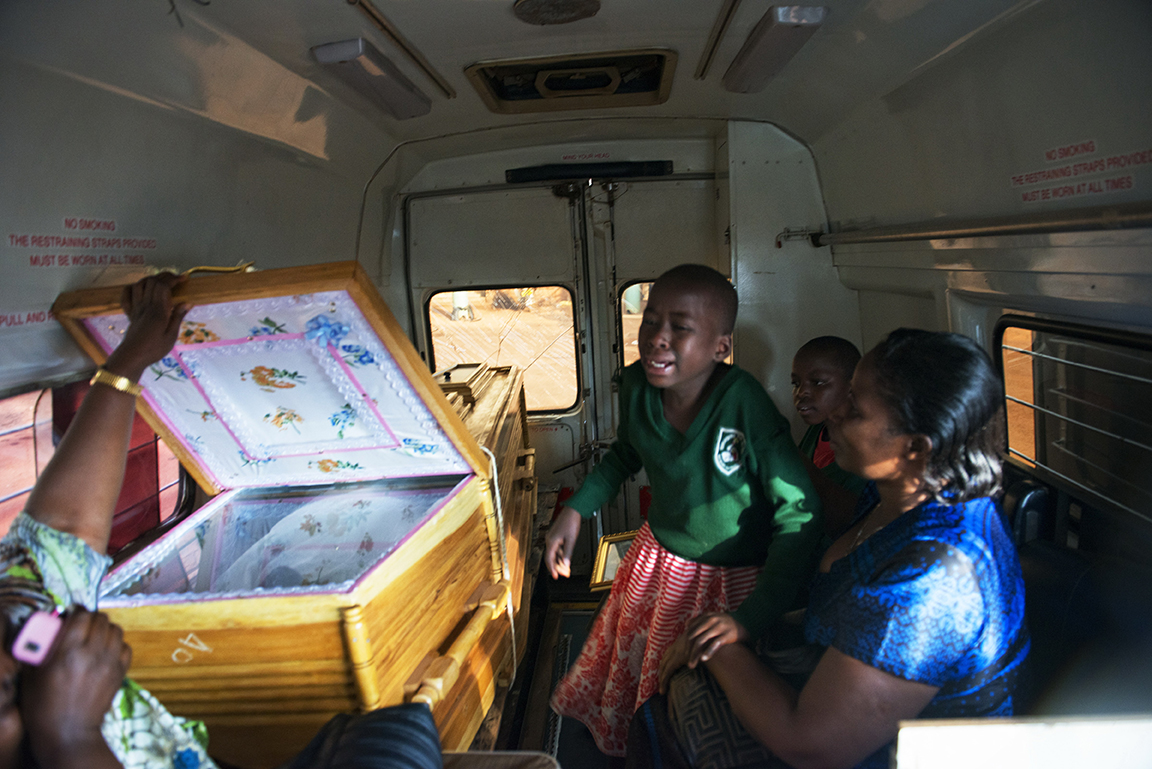 Edith Kemigisha, 9, screams and weeps as she looks at the dead body of her mother, Jolly Komurembe, 38, hours after she died of advanced breast cancer and before being transported to her village for burial in Western Uganda, in Kampala, Uganda, July 21, 2013.  Jolly, who has four children with her husband Robert, found a tumor around two years before while living in the western Uganda district of Rukunghiri. Like so many women in Uganda who don't seek medical care for diagnosis and treatment in the early stages of Cancer, Jolly's cancer was advanced when she finally had a mastectomy in January 2013.  These images depict the final week of her life.