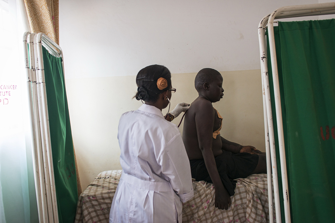 Breast Cancer patient Jessy Acen, 30, is examined by Dr. Victoria Mwebe, 26, before Jessy receives chemotherapy at the Cancer Institute attached to the Mulago Hospital, in Kampala, Uganda, July 22, 2013.  Jessy, who has two children living with relatives in the northern district of Gulu,  found a tumor in her breast in 2008, and eventually went to a medical center in Gulu for diagnosis. Her case was disregarded by doctors in Gulu, and after persisting, Jessy was finally sent to the Mulago Hospital in Kampala for treatment.  Like so many women in Uganda who don't seek medical care for diagnosis and treatment in the early stages of Cancer, or who are misdiagnosed by medical staff around the country, Jessy's cancer was advanced when she finally had a mastectomy.  Jessy sleeps at the hospital for several weeks while receiving chemotherapy because she could not afford the $10. bus fare back to Gulu.