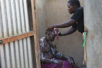 Breast Cancer patient Jessy Acen, from Gulu, is is bathed by her sister in Pece Vanguard, on the outskirts of Gulu, Uganda, July 23, 2013.  Jessy, who has two children living with relatives in the northern district of Gulu,  found a tumor in her breast in 2008, and eventually went to a medical center in Gulu for diagnosis. Her case was disregarded by doctors in Gulu, and after persisting, Jessy was finally sent to the Mulago Hospital in Kampala for treatment.  Like so many women in Uganda who don't seek medical care for diagnosis and treatment in the early stages of Cancer, or who are misdiagnosed by medical staff around the country, Jessy's cancer was advanced when she finally had a mastectomy.  Jessy sleeps at the hospital for several weeks while receiving chemotherapy because she could not afford the $10. bus fare back to Gulu.