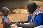Breast Cancer patient Jessy Acen, from Gulu, plays tenderly with one of her sons, Jered Kakanyero, 4, as he caresses her swollen arm and hand in Pece Vanguard, on the outskirts of Gulu, Uganda, July 23, 2013.  Jessy Acen first discovered a lump in her breast in 2009. She traveled from her home in Gulu to Mulago Hospital in the Ugandan capital of Kampala to have her diagnosis of breast cancer confirmed. She began chemotherapy soon after but, unable to afford the cost of transport the 300 km from Gulu to Kampala, she was forced to stop treatment. By the time she'd returned to Mulago in 2011 her cancer had spread to her lymph nodes, liver and lungs.