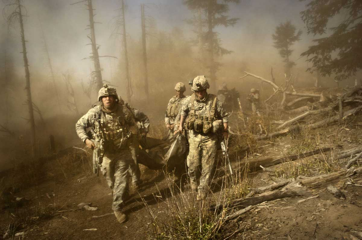 U.S. troops carry the body of Staff Sgt. Larry Rougle, who was killed when the insurgents ambushed their squad in the Korengal Valley. Soldiers with the 173rd battle company, on a battalion mission in the korengal valley in the village of Yakachina. 2008