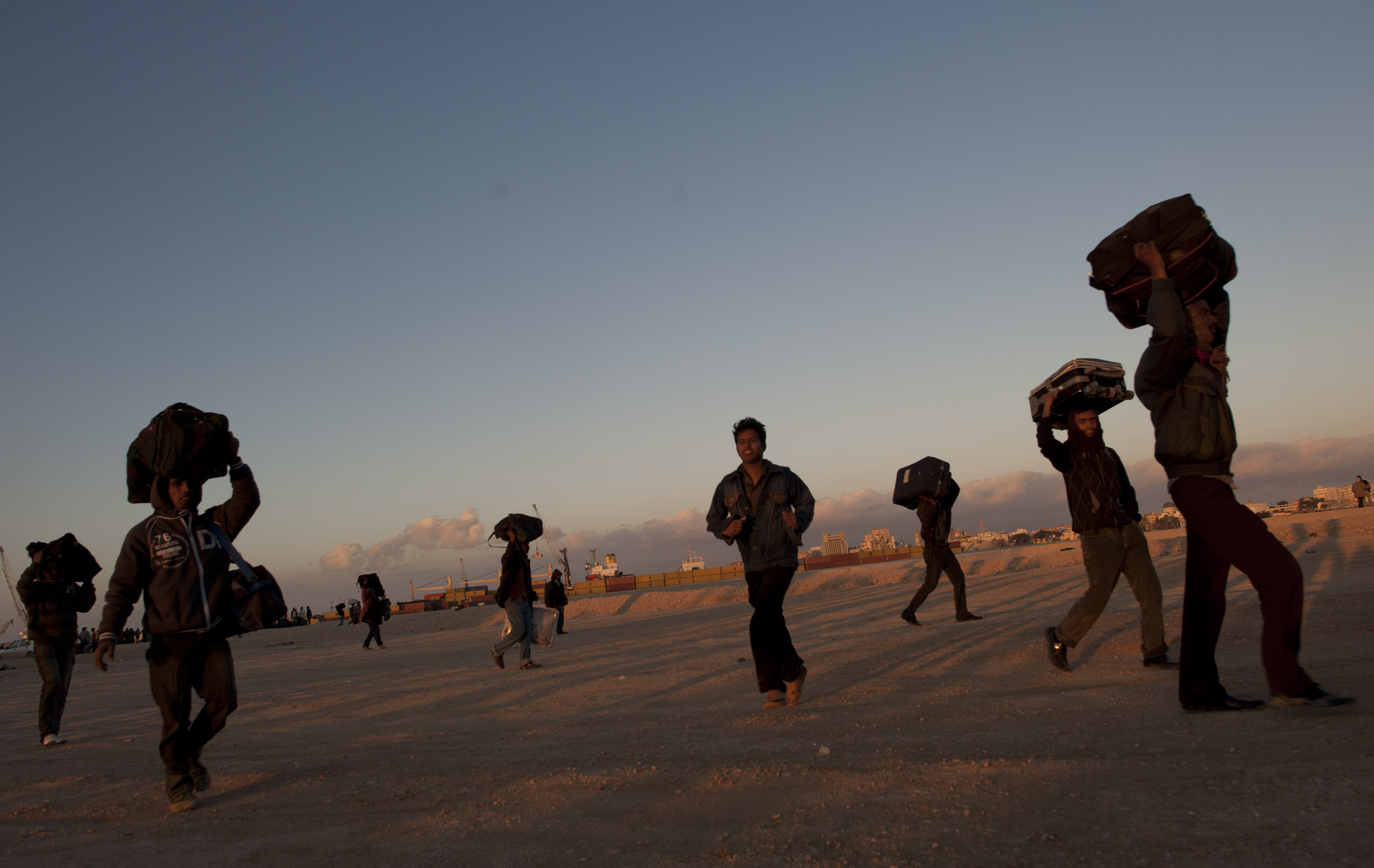 Bangladeshi workers carry their luggage across the grounds of the port in search of a ship to take them out of Benghazi, in Eastern Libya, as the fighting continues between opposition forces and those loyal to Col. Qaddafi across Libya, February 28, 2011. Thousands of workers living in Libya of various nationalities have fled the fighting across the country.