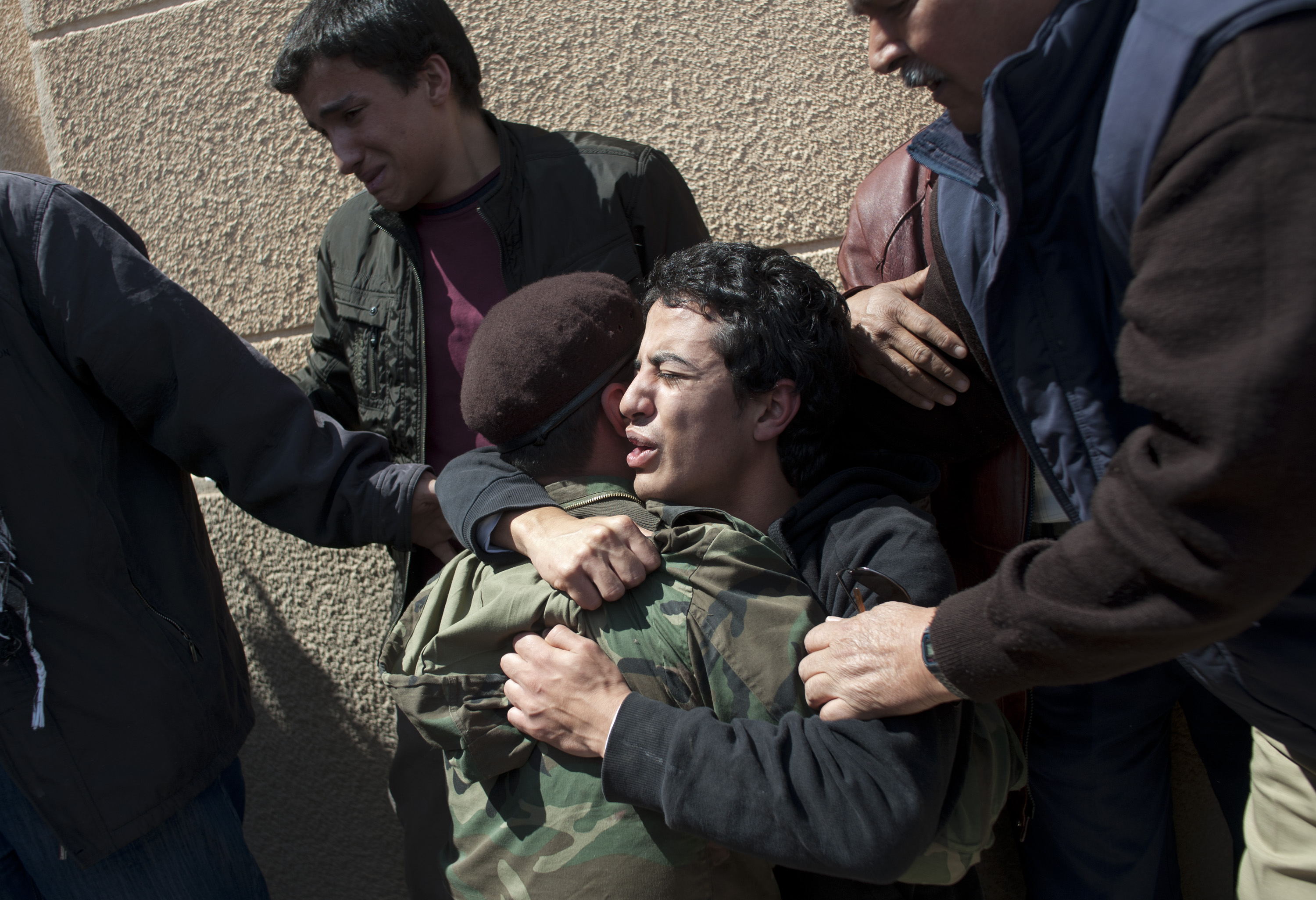 Relatives of Emad al Giryani weep over his body during his funeral the day after he was killed in fighting on the frontline in Ras Lanuf, in Eastern Libya, March 12, 2011. Dangerous confrontations have been going on between opposition forces and those loyal to Col. Qaddafi across Libya.