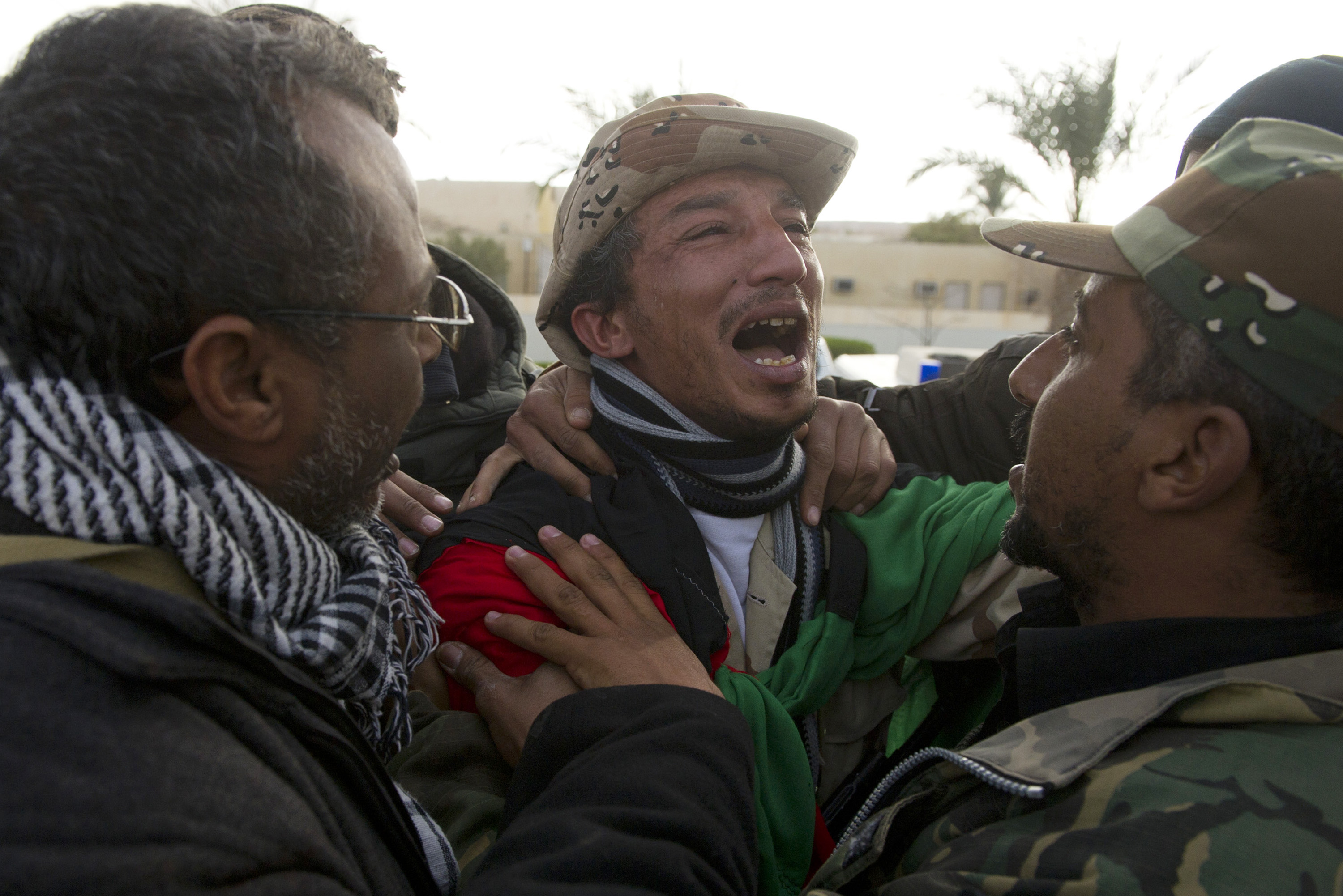 Opposition troops weep at the hospital in Ras Lanuf as soldiers are being brought in from the frontline west of Ras Lanuf during heavy fighting between troops loyal to Qaddafi in Ras Lanuf, in Eastern Libya, March 9, 2011. Dangerous confrontations have been going on between opposition forces and those loyal to Col. Qaddafi across Libya.