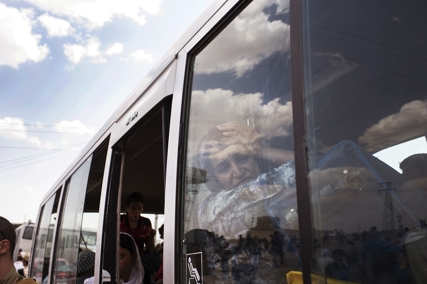 A woman waits on a bus as thousands of Syrians who crossed from Syria into Northern Iraq at the Sahela border point scramble to get onto buses destined for refugee camps in Erbil, in Dahuk, Northern Iraq, August 21, 2013.  The United Nations High Commission for Refugees estimates that over 30,000 Syrians have crossed into Northern Iraq since the border was re-opened last week, and roughly three to four thousand continue to cross daily.  The mostly ethnically Kurdish refugees are fleeing increasing insecurity, economic strife, and a shortage of electricity, water, and food in their areas. (Credit: Lynsey Addario for The New York Times)