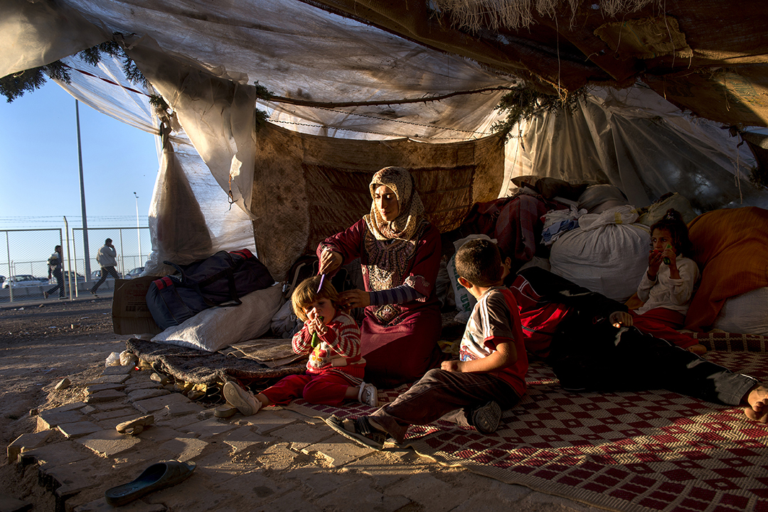 Iman Zenglo, 30, sits with her five children in their tent she and her husband set up roughly three months prior in squalid conditions in a squatters camp outside of the Killis camp on the Turkish side of the Turkish Syrian border in Turkey, October 22, 2013.  Many Syrian refugees cross back and forth from Syria into bordering countries to work as laborers and visit family across borders.  Syrian refugees now total over 2,000,000 in countries neighboring Syria as the civil war rages for the third year.