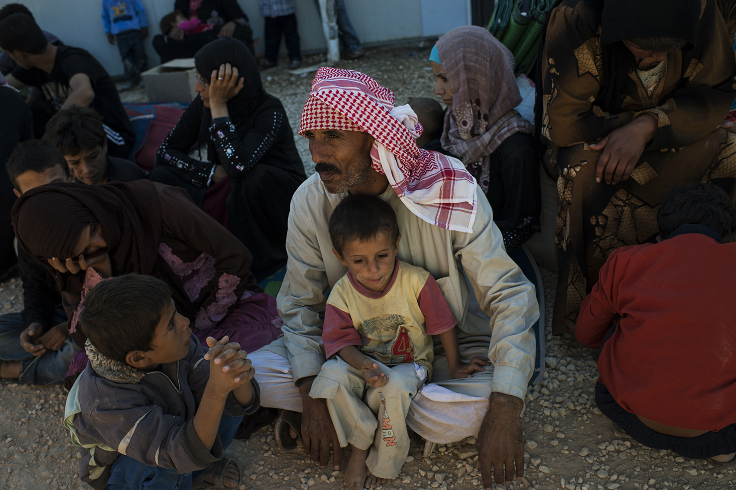 Ayed, 45, a Syrian refugee from Homs, sits with two of his 7 children the morning after crossing into Jordan from Syria, at the United Nations High Commission for Refugees reception center in Zaatari Camp, in Jordan, September 16, 2013. There are an estimated 600,000 refugees in Jordan, and two million refugees in countries bordering Syria as Syria's civil war rages in its third year