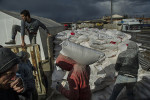 Turkish workers load bags of flour provided by the Turkish Red Crescent onto a truck bound for Syria, at the Turkish Syrian border, in Kilis, Turkey, February 11, 2013.  Roughly 800,000 Syrians have been displaced to neighboring countries by the fighting across Syria, and the aid to refugees has been marred by politics. The United States claims it has donated millions of dollars to Syria in aid, though there has been little visible sign of it across northern Aleppo Province.   Two years into the country's uprising and civil war, there is a massive need for humanitarian aid--both food and non-food items--across Syria.