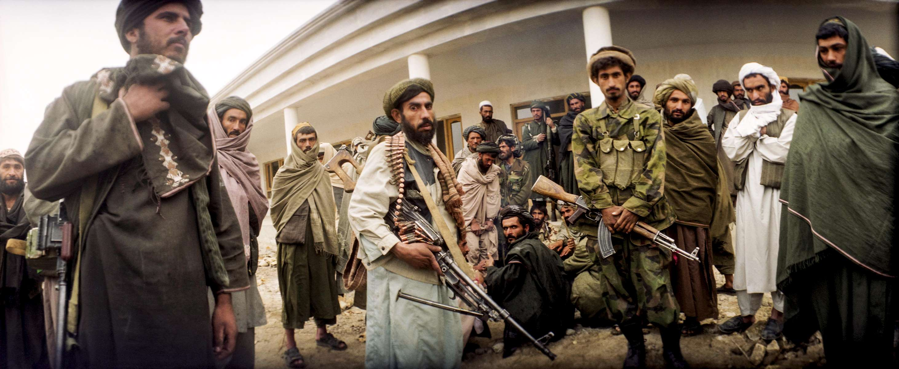 Men stand outside the governor's house hours after the fall of the Taliban,in Kandahar, December 2001.