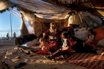 Iman Zenglo, thirty, sits with her five children in the squalid conditions of theirsquatters tent outside the Kilis camp on the Turkish side of the Turkish-Syrianborder, October 2013.