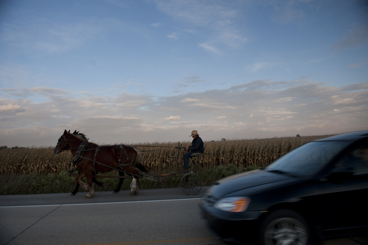 A car passes an Amish horse and buggy near Newtown, Iowa. September 30, 2011