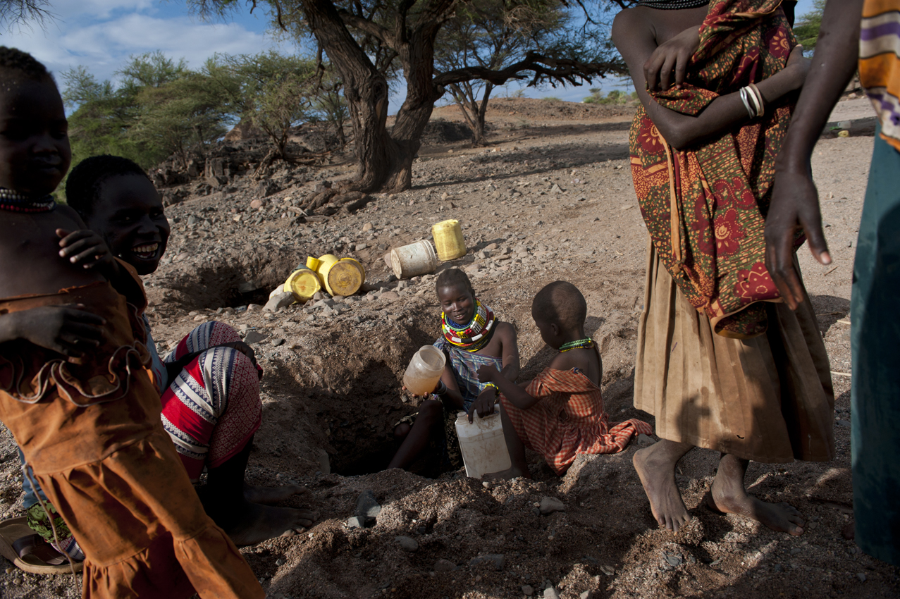 Kenyan women pull water out from a hole in the ground the morning after it rained for the first time in over a year in the region, in Sesame, in Turkana, Kenya, August 14, 2011. The horn of Africa is suffering one of the worst droughts in years, displacing thousands, and killing others through severe malnutrition.