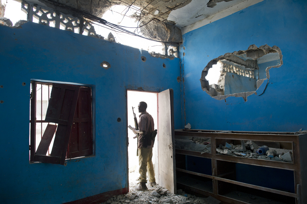 Somalis guards walk through the rubble of the former frontline between Ugandan troops and Al Shabaab in the Ali Kameen intersection in the city of Mogadishu, Somalia, August 25, 2011.  Thousands of Somalis have traveled to neighboring countries and to the capital city of Mogadishu to escape extreme drought conditions in their villages--an estimated 1.7 million people have become drought displaced, according to an UNOCHA report. The horn of Africa is suffering one of the worst droughts in years, displacing thousands, and killing others through severe malnutrition, measles, and diarrhea.