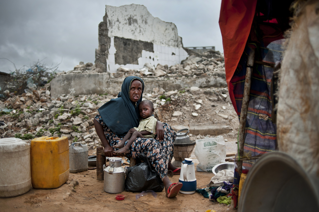 Aminacido Sheikh sits with one of her four children after arriving from the Yaksheet district 25 days ago to live with other Somalis amisdt the ruins of buildings and in dire conditions in the Badbadoo camp for internally displaced in Mogadishu, Somalia, August 29, 2011.  Aninacido says 'We haven't received any rations. I don't know how to explain how we feed our children. My husband goes in the morning and comes back with food.' Thousands of Somalis have traveled to neighboring countries and to the capital city of Mogadishu to escape extreme drought conditions in their villages--an estimated 1.7 million people have become drought displaced, according to an UNOCHA report. The horn of Africa is suffering one of the worst droughts in years, displacing thousands, and killing others through severe malnutrition, measles, and diarrhea.