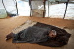 A boy lies immobile, ill with measles, in a camp for internally displaced Somalis on a morning where at least five children were being buried at dawn in this camp, after succumbing to measles in Mogadishu, Somalia, August 27, 2011.  Locals claim that at least five children are dying per day because of the poor conditions in the camps--measles, malnutrition, and dehydration contributing to some of the highest numbers of deaths. Thousands of Somalis have traveled to neighboring countries and to the capital city of Mogadishu to escape extreme drought conditions in their villages--an estimated 1.7 million people have become drought displaced, according to an UNOCHA report. The horn of Africa is suffering one of the worst droughts in years, displacing thousands, and killing others through severe malnutrition, measles, and diarrhea.