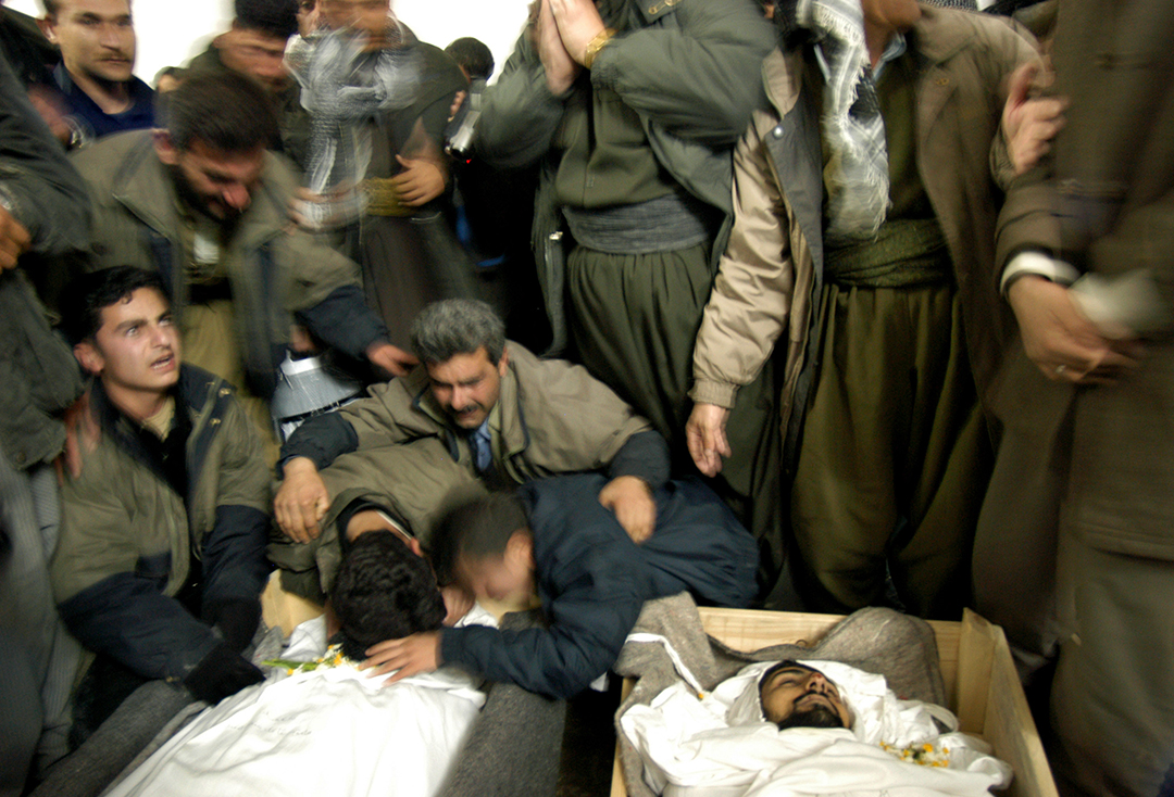 Friends and relatives stand over the bodies of some of five men killed in a shoot out at a PUK checkpoint in Suleimaniya, Northern Iraq March 5, 2003.  The five men had long beards, and were accused of being Ansar fundamentalists.